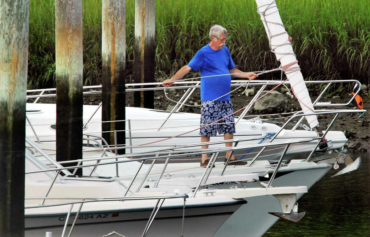 Bruce Johnson ties down his sails in anticipation of Hurricane Henri at Halloween Yacht Club in Stamford on Friday. Henri is expected to hit Connecticut over the weekend causing coastal flooding and wind gusts up to 60 mph.