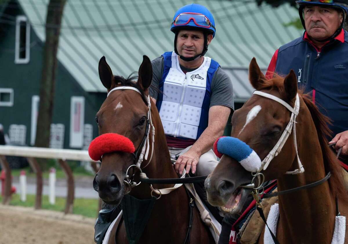 Letruska, left, with exercise rider Victor O'Farrell, goes out for her morning exercise with a lead pony ridden by trainer Juan Gutierrez at Saratoga Race Course on Friday, Aug. 20, 2021, in Saratoga Springs, N.Y. Letruska will be entered in the Personal Ensign next Saturday.