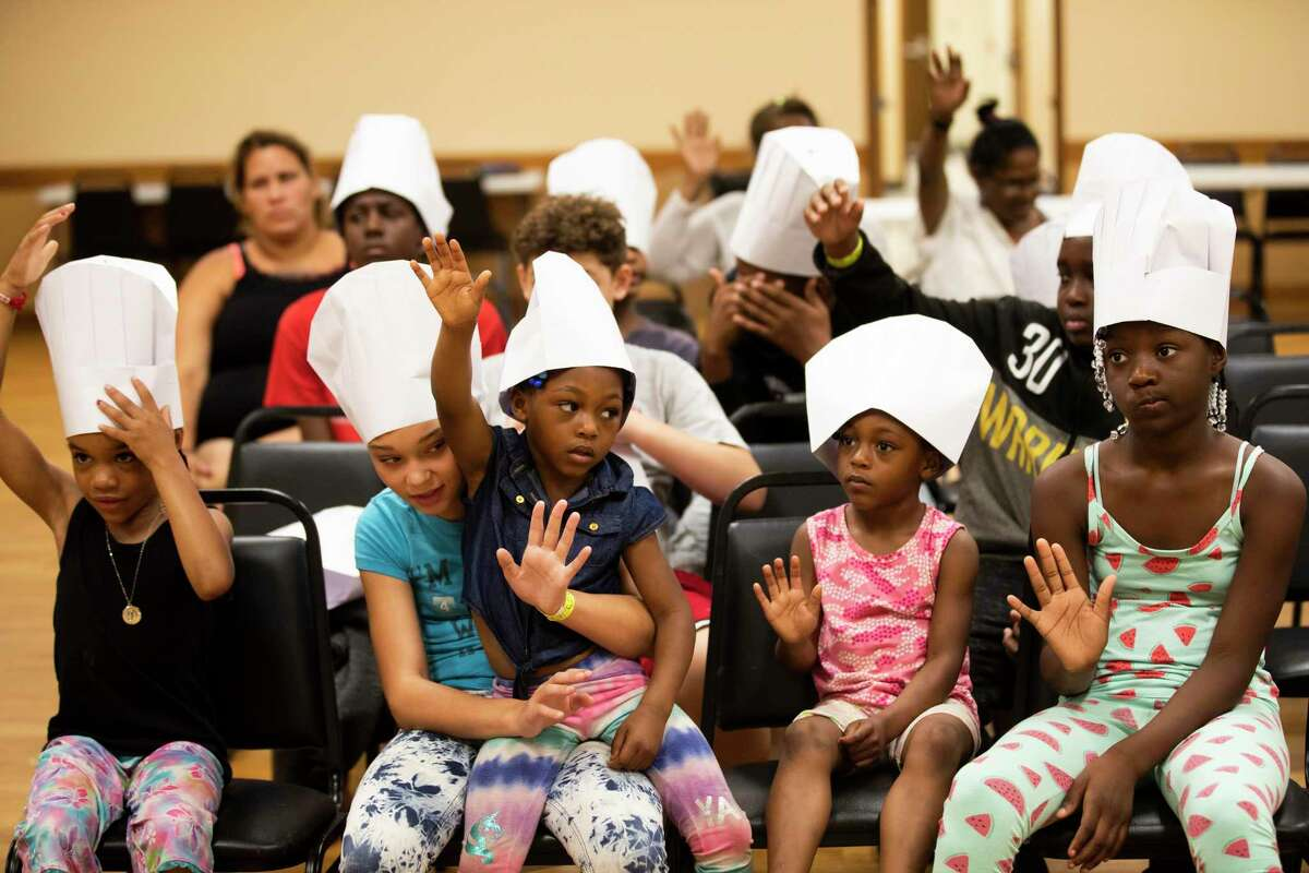 A group of kids from Cuney Homes and Kelly Village Apartments raise their hands after being asked if they liked apples during a beginner's cooking class during the End of Summer Meals Matter program organized by the non-profit organization, Kids Lives Matter on Monday, July 29, 2019, in Houston. The group of children were learning how to prepare healthy chicken tacos while also learning about the four food groups.