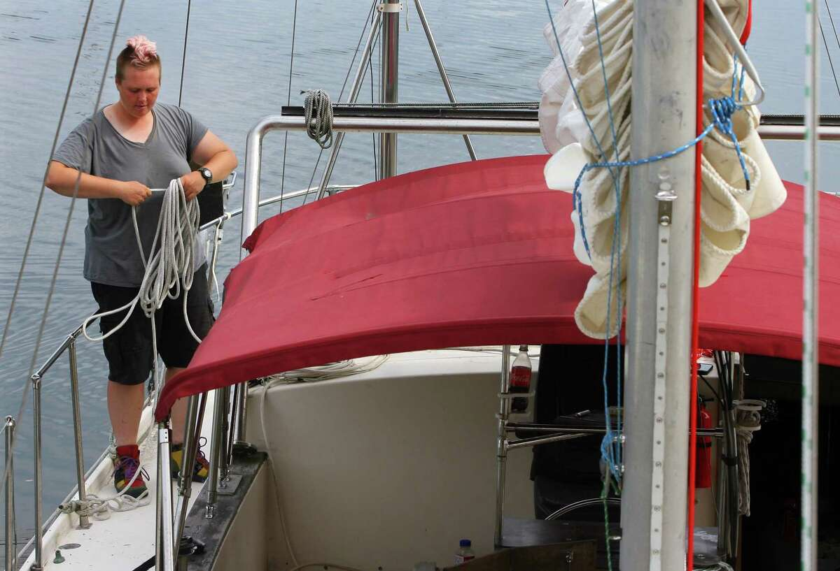 Ivy Spillman stows a line while hanging out on a yacht she gets to use at Harbor Point Marina in Stamford, Conn., on Friday August 20, 2021. The region will be bracing for Hurricane Henri, which is expected to hit Connecticut over the weekend causing coastal flooding and wind gusts up to 60 mph.
