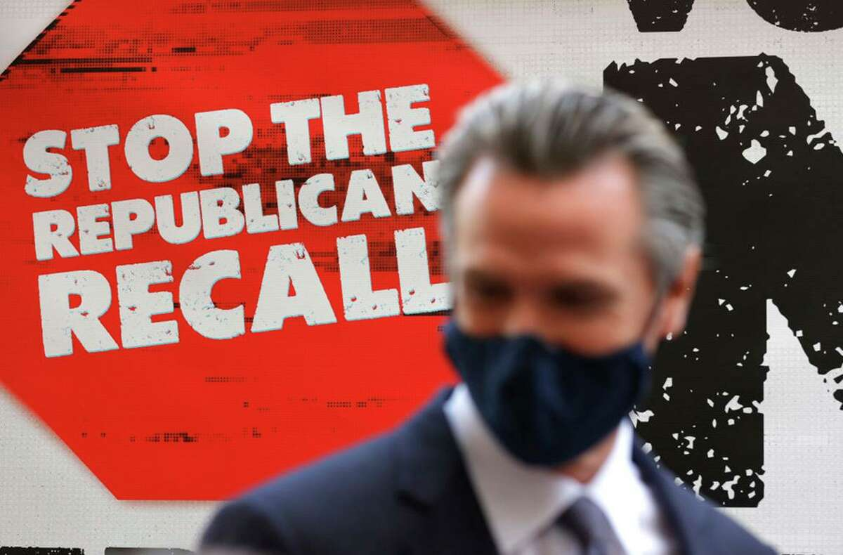 A sign against the recall is posted behind California Gov. Gavin Newsom on Aug. 13 in San Francisco.