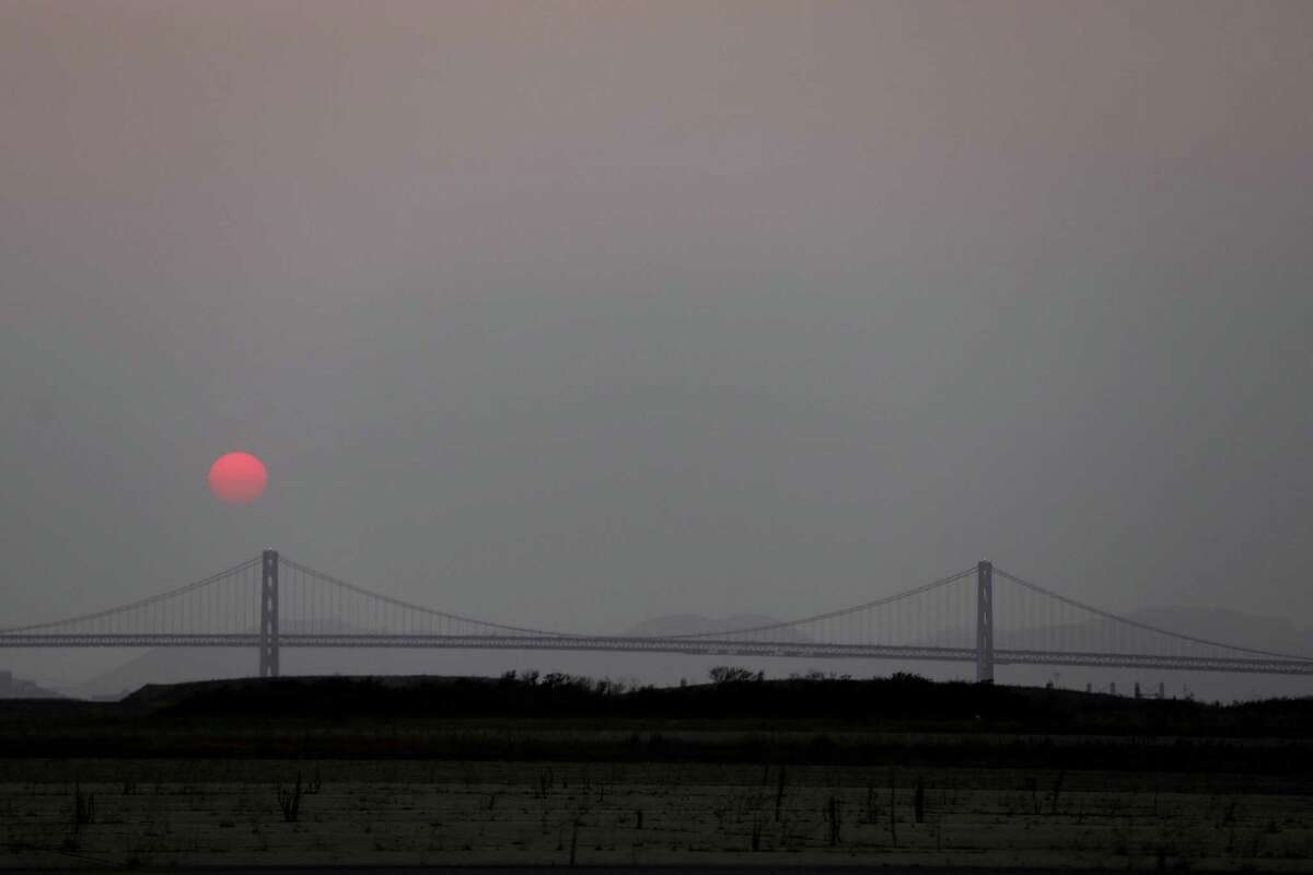 An orange sun sets in a hazy sky near the Bay Bridge, seen from Alameda, on Wednesday. The Bay Area Air Quality Management District issued a Spare the Air alert for Thursday and Friday as smoke from Northern California wildfires drifted into the region.