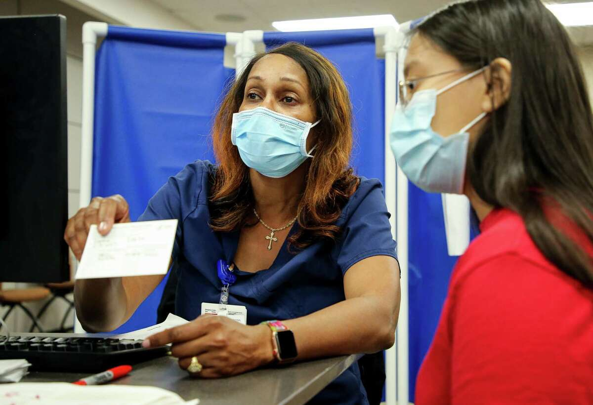 Registered nurse Sharon Cherry, center, instructs Emilia López, 14, on when to return for her second dose of the Pfizer COVID-19 vaccine at Houston Methodist Sugar Land Hospital on Thursday, July 22, 2021, in Sugar Land. Fort Bend County vaccination rate ranks among the highest in the state, although vaccinations have slowed down as demand has dropped after the early success. The county is currently trying to reach those unvaccinated through community outreach and have been met with some critics who say the $345,000 federally-funded program is a waste of money. Supporters say outreach remains important because some people lack access, information or the opportunity to get the vaccine still.