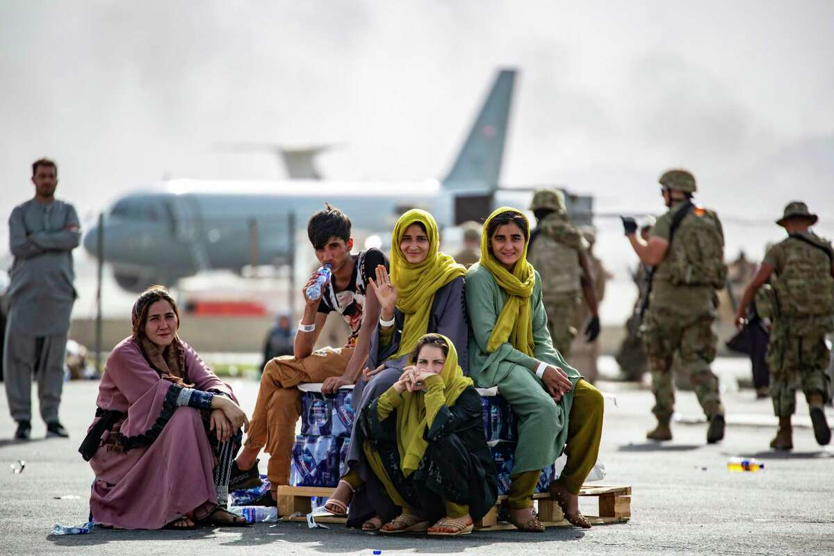 In this image provided by the U.S. Marines, evacuee children wait for the next flight after being manifested at Hamid Karzai International Airport, in Kabul, Afghanistan, Thursday, Aug. 19, 2021.