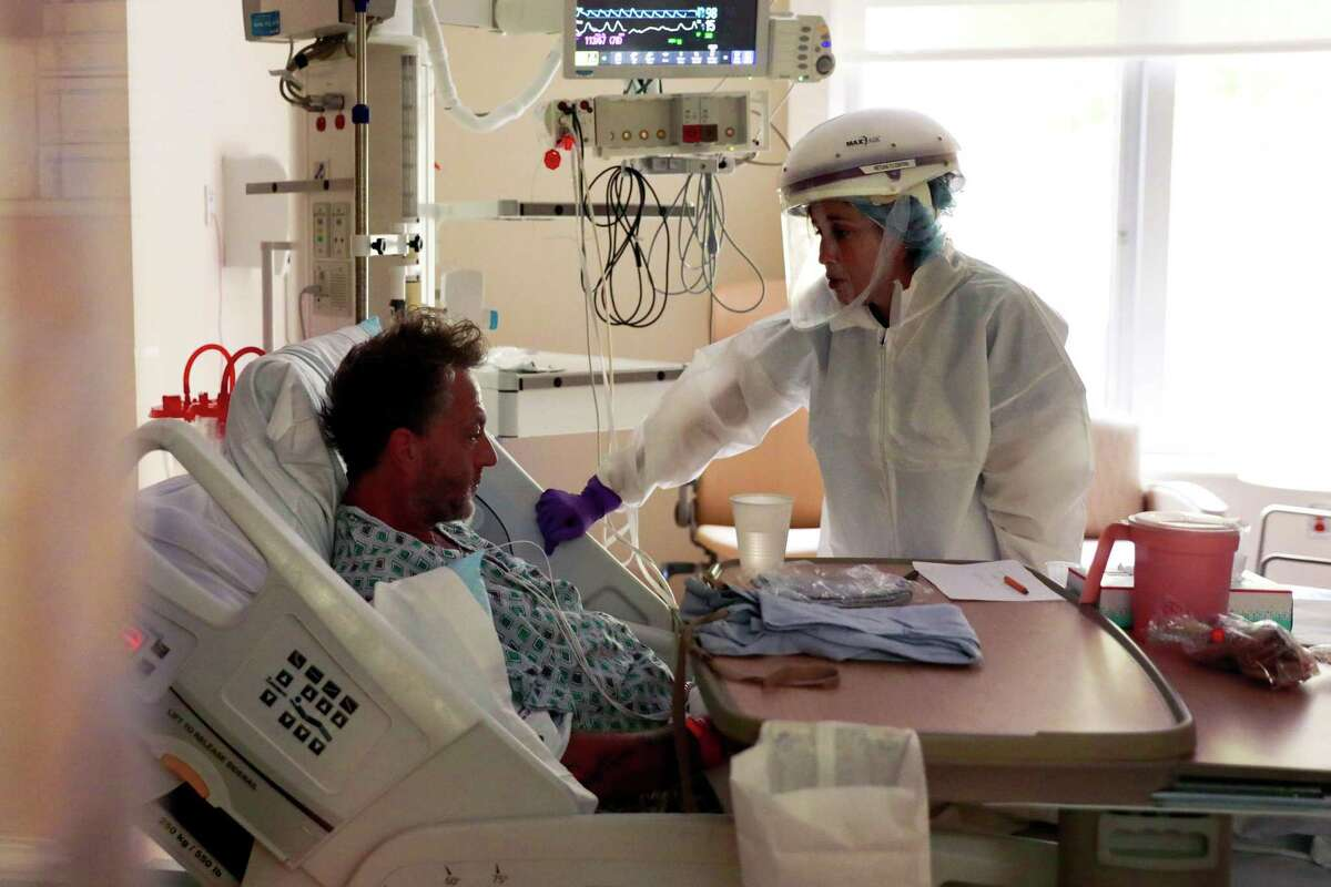 Nurse Shannon Baker (right) chats with COVID-19 patient David Gray, 51, in a negative pressure room at El Camino Hospital on Wednesday in Mountain View, California.