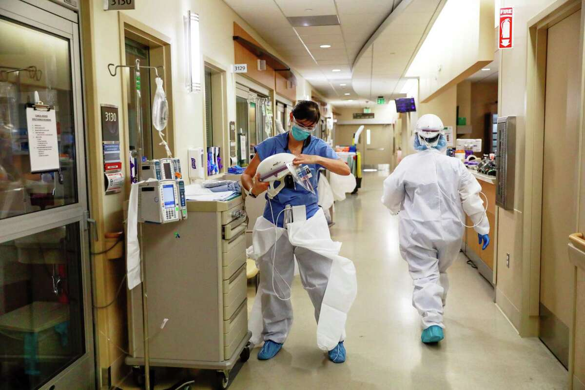 Nurse Shannon Baker (left) dons protective gear before seeing a COVID-19 patient in an isolation room at El Camino Hospital in Mountain View.