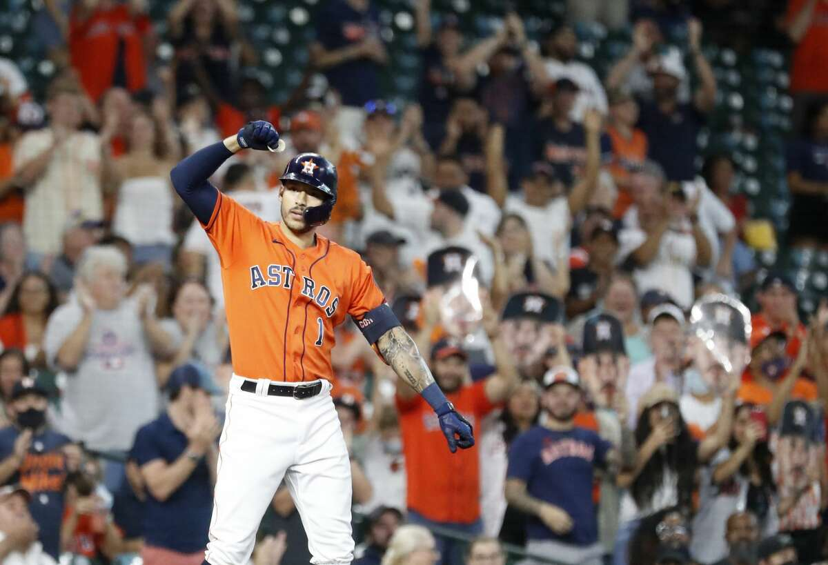 Houston Astros Carlos Correa (1) celebrates on third base after hitting a triple off Seattle Mariners starting pitcher Yusei Kikuchi during the first inning of an MLB baseball game at Minute Maid Park, Friday, August 20, 2021, in Houston.