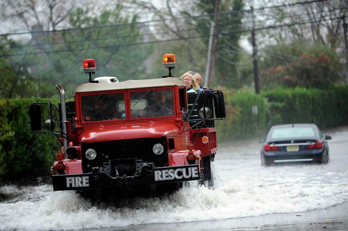 A fire rescue truck from Sound Beach Volunteer Fire Department helps people during the hurricane Sandy on Shore Road in Old Greenwich Monday Oct. 29, 2012. The City of Groton asked some residents to voluntarily evacuate in preparation for Tropical Storm Henri.