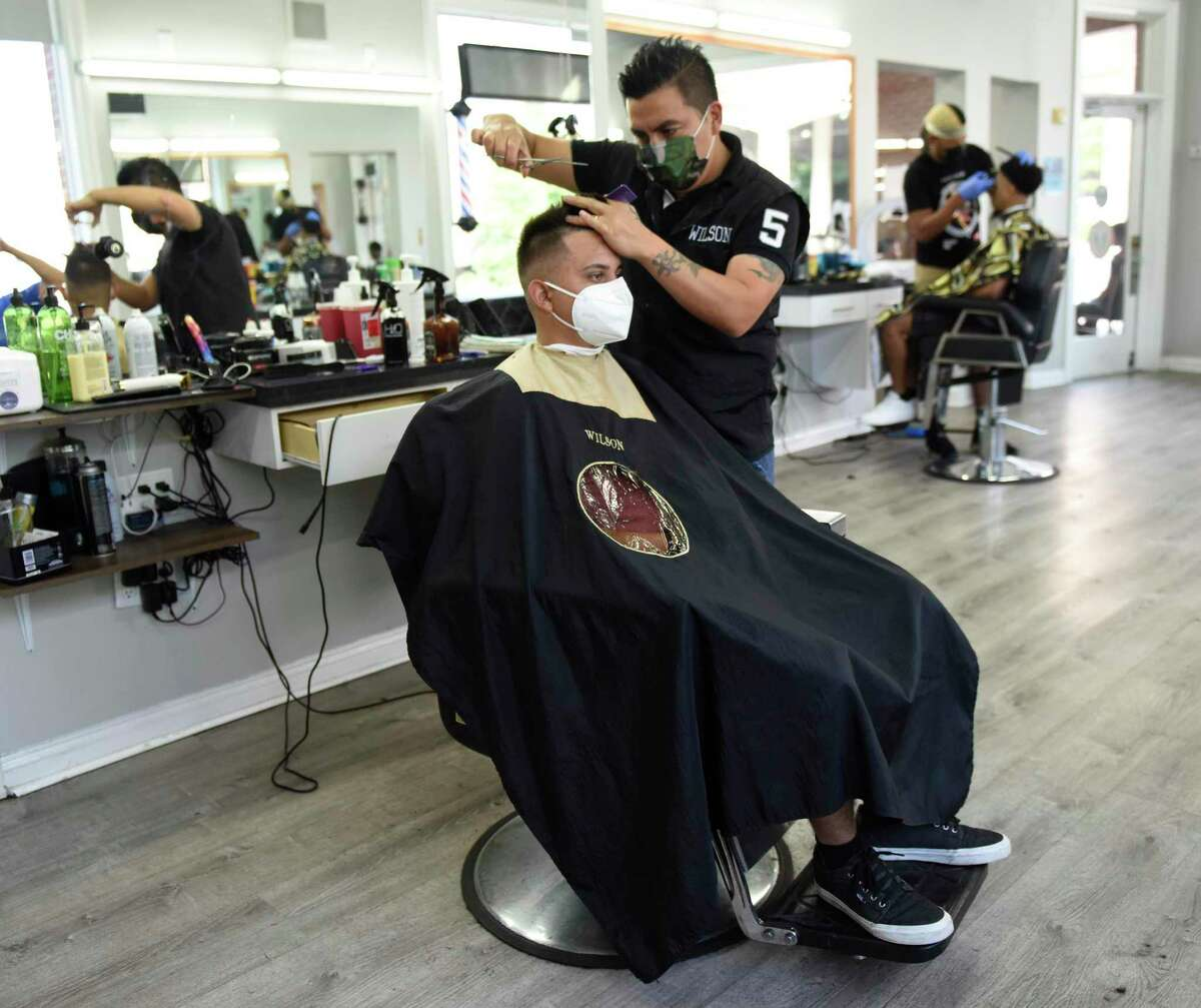 """Barber Wilson Castro gives a haircut to Fairfield's Mauro Delgado at Stamford Barbershop in Stamford, Conn. Wednesday, Aug. 11, 2021. Stamford Barbershop hosted a kickoff event last weekend for the city's """"barbershop initiative"""" program to start more informed conversations about the COVID vaccines between stylists, barbers, and their clients."""