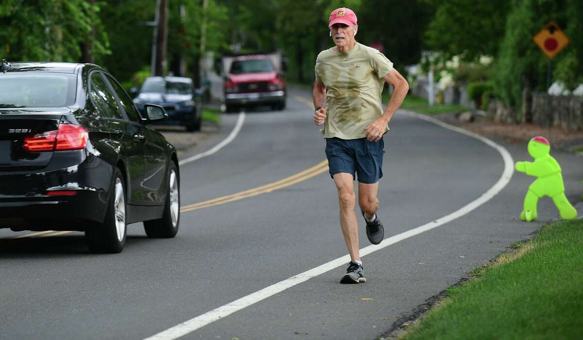 A jogger runs along Shore Road Thursday, August 19, 2021, in Greenwich, Conn. Resident Maggie Bound is leading a community effort to demand town action on what she considers to be a very dangerous intersection in Old Greenwich.