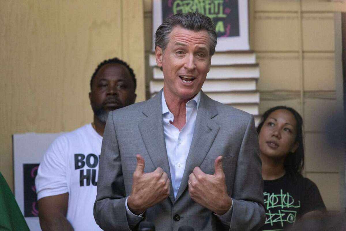 Governor Gavin Newsom Speaks at a press conference in the backyard patio of Graffiti Pizza on Thursday, June 17, 2021 in Oakland, Calif. In the background are Beastmode Barbershop owner Tyranny Allen and Graffiti Pizza owner Davina Dickens.