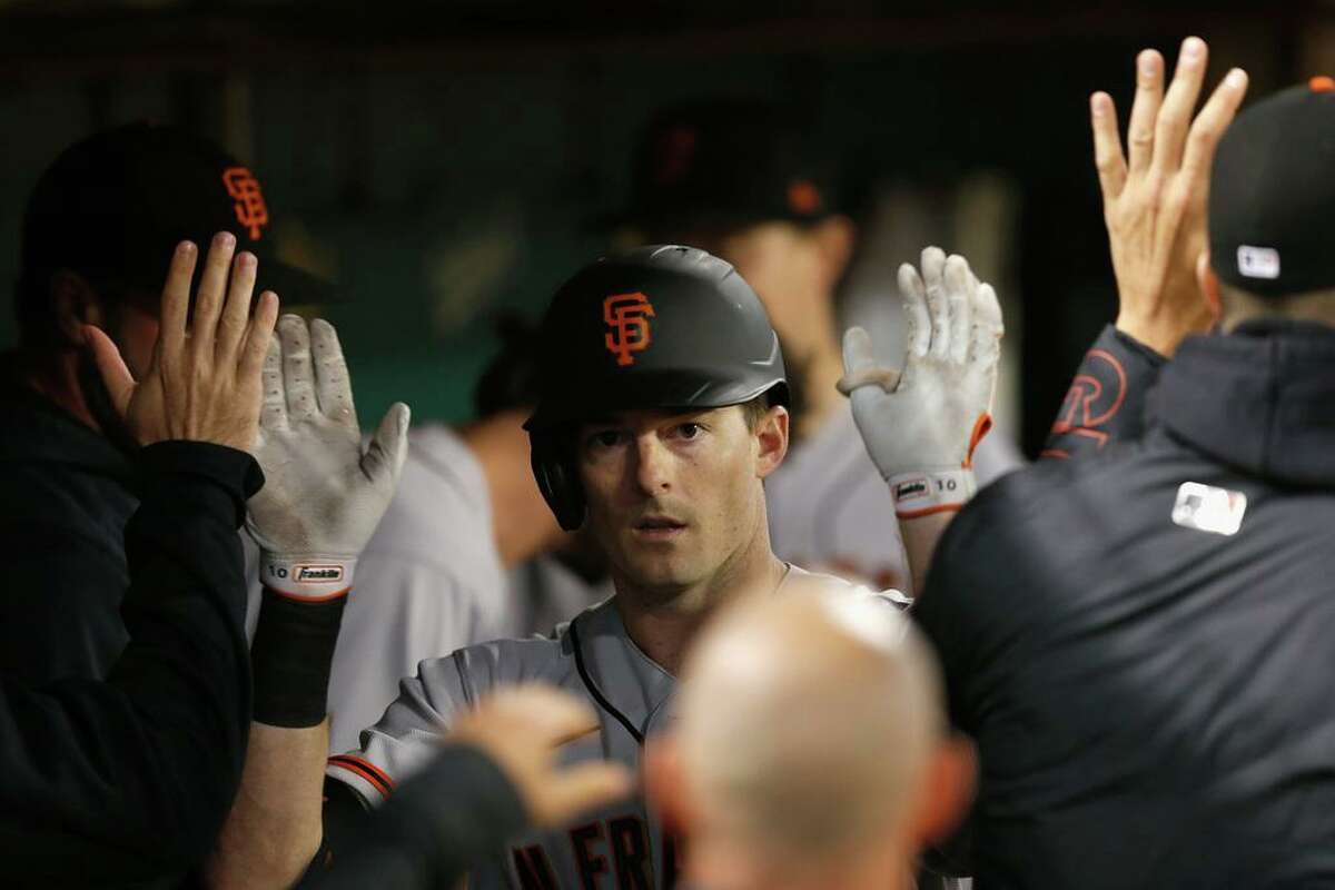OAKLAND, CALIFORNIA - AUGUST 20: Mike Yastrzemski #5 of the San Francisco Giants celebrates in the dugout after hitting a solo home run in the top of the fifth inning against the Oakland Athletics at RingCentral Coliseum on August 20, 2021 in Oakland, California. (Photo by Lachlan Cunningham/Getty Images)