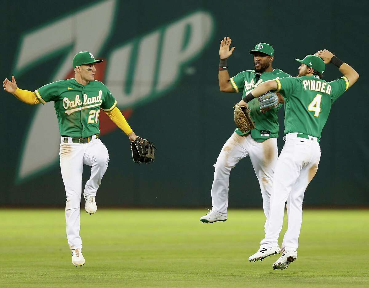 Outfielders Mark Canha (left) Starling Marte and Chad Pinder celebrate the A's win over the Giants in Oakland.