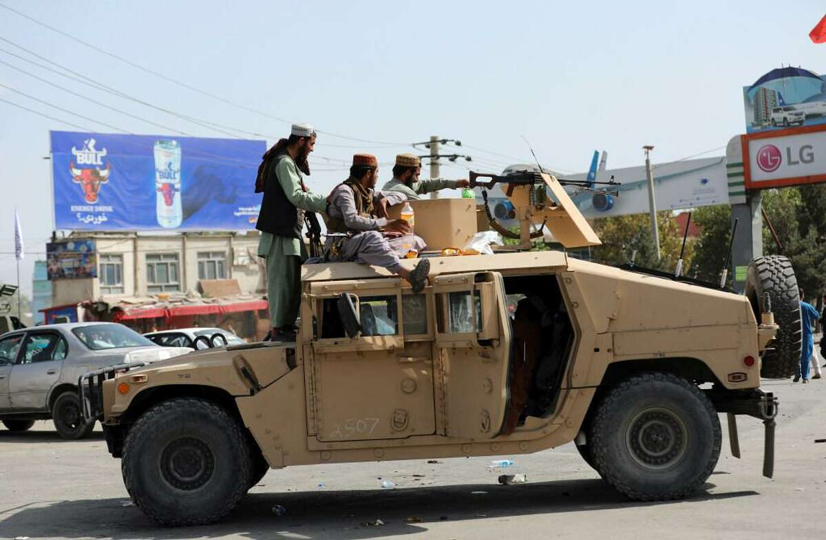 Taliban fighters stand guard in front of the Hamid Karzai International Airport in Kabul.