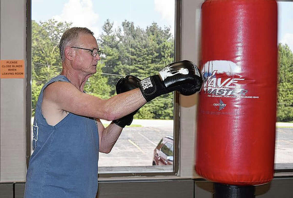 Dave Mumford lands a jab against a punching bag Friday during a Rock Steady boxing class at Bob Freesen YMCA. The class helps improve balance, strength and quality of life for those fighting Parkinson's disease.