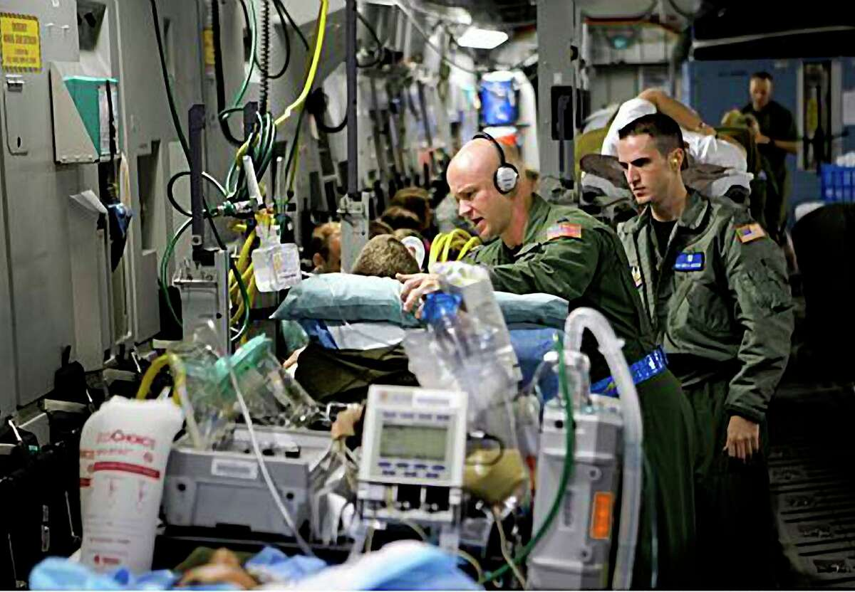 Capt. Darrell W. Saylor (left) and Staff Sgt. Brett Anderson, part of a critical care and transport team, tend to the critically wounded who are being flown from Ramstein Air Base in Germany to Andrews Air Force Base in Maryland.
