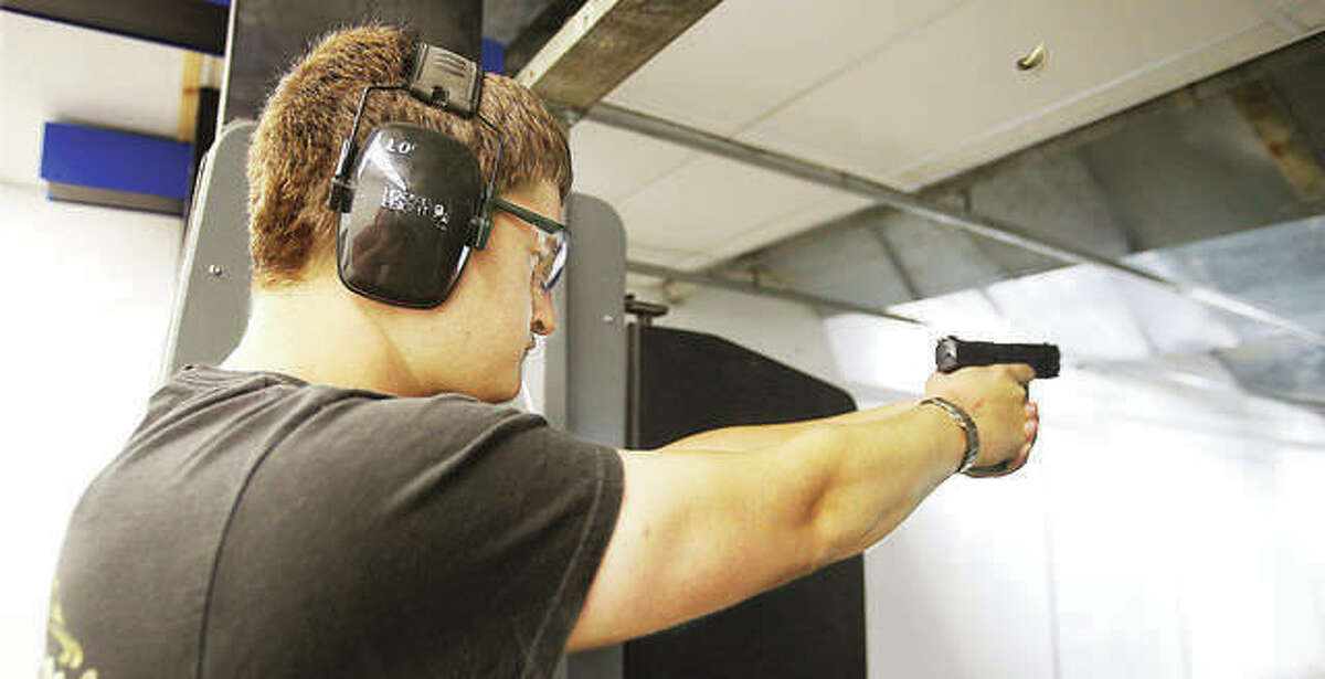 An employee of Piasa Armory in August 2018 fires a handgun in the business' firing range last year. The armory is holding an open house event today from 10 a.m.-4 p.m. at the store at 3685 E. Broadway.