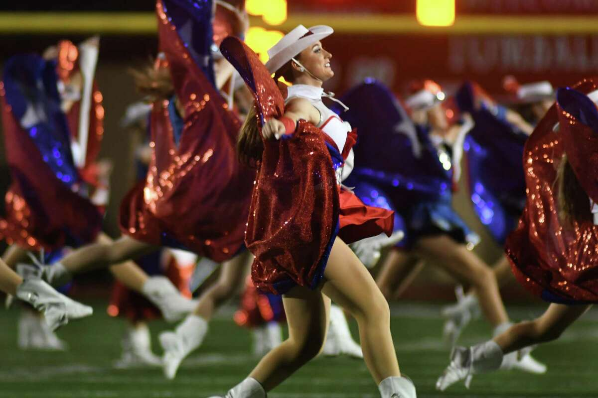"""Kailey Lambert, a Tomball High School senior and her fellow members of the THS Cougar Charms, along with the Tomball Memorial Silver Stars, performs a routine to """"Deep in the Heart of Texas"""" during halftime of the non-district football season opener between Tomball Memorial and Tomball at Tomball Stadium on August 30, 2019."""