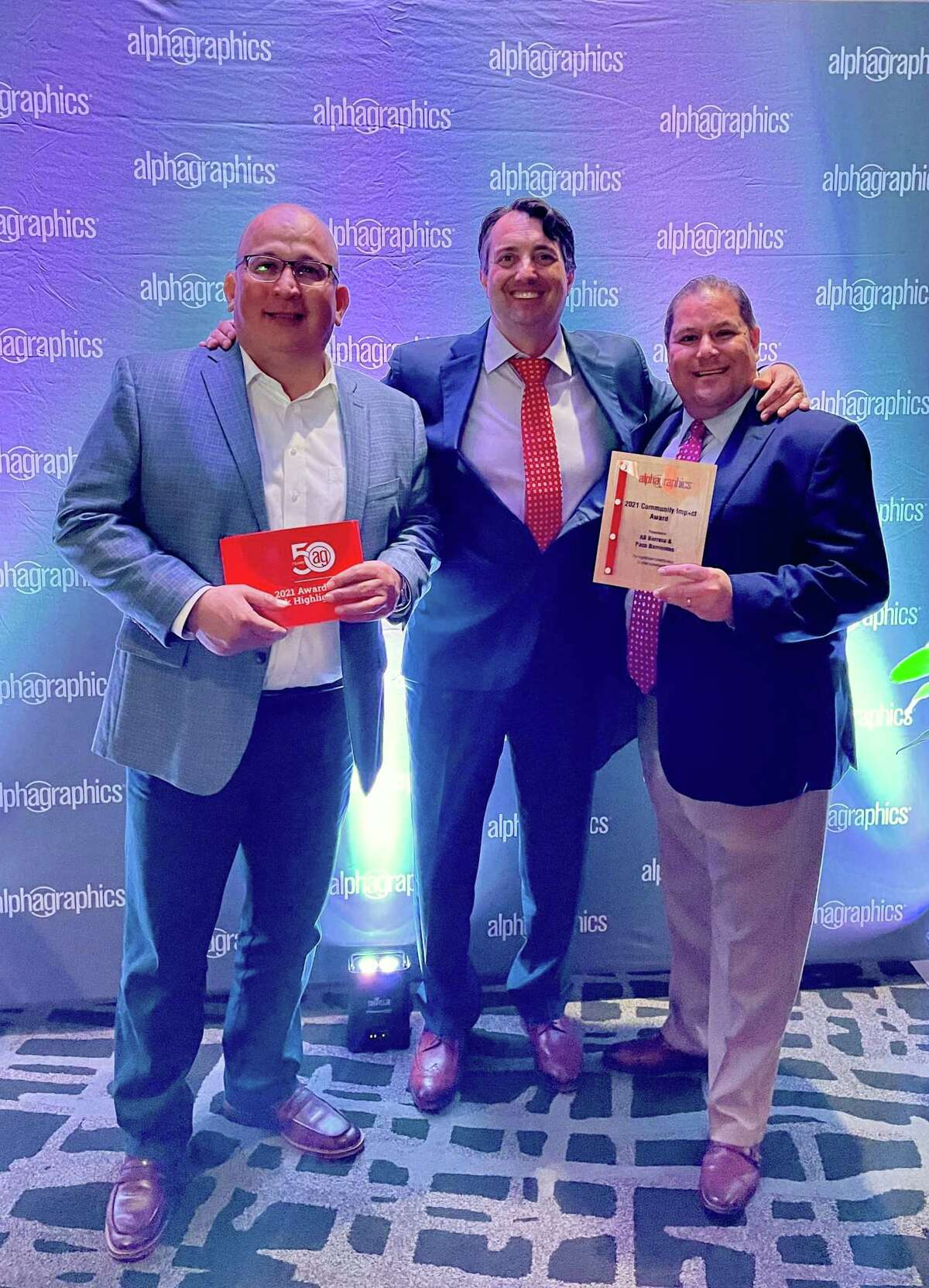 Local AlphaGraphics franchisees A.B. Barrera and Paco Barrientos pose with AlphaGraphics President Ryan Farris.