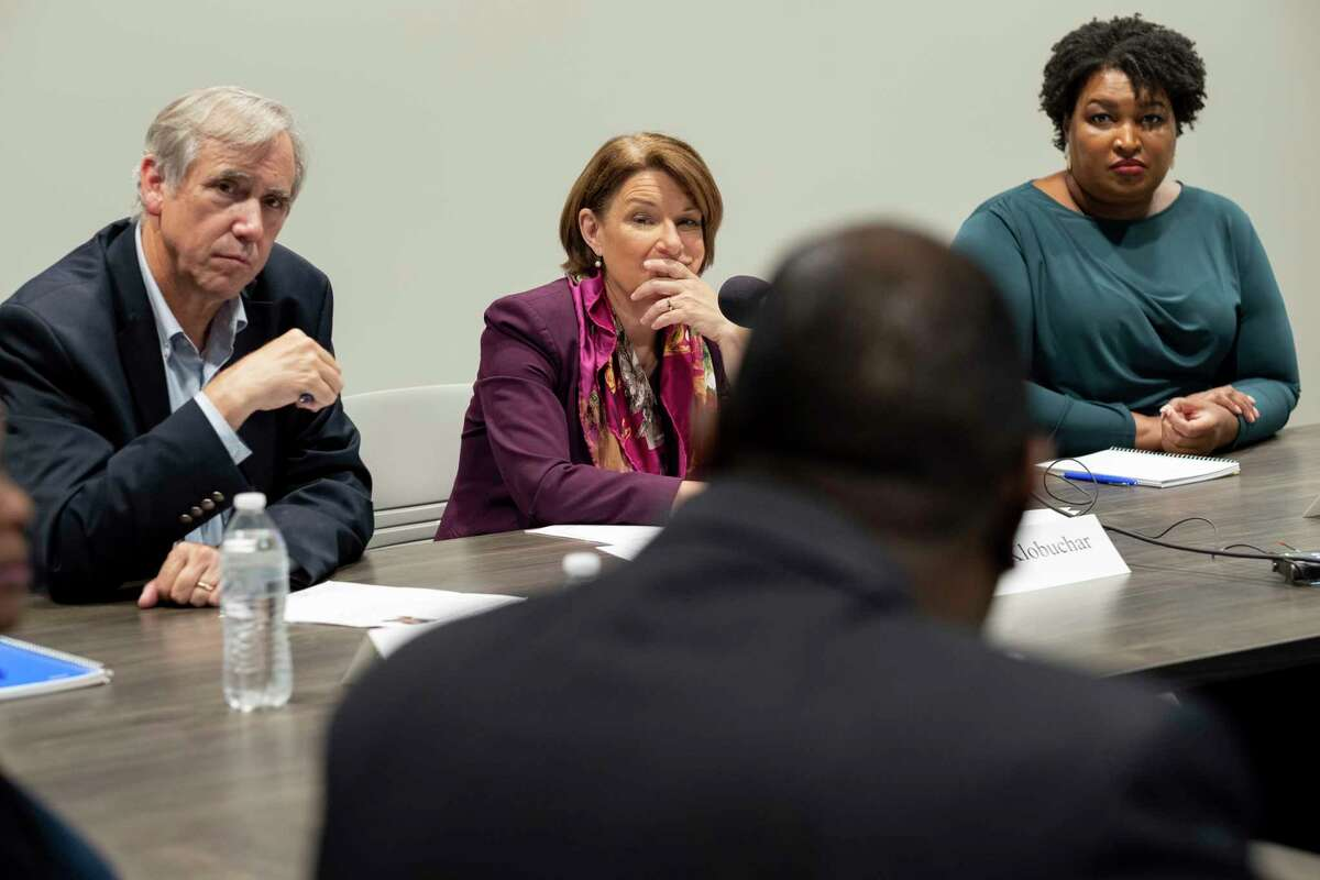 FILE - In this July 18, 2021, file photo, Sen. Jeff Merkley, D-Ore., from left, Sen. Amy Klobuchar, D-Minn., and former Georgia state Rep. Stacey Abrams, right, listen to people talk about their experiences in voting, in Smyrna, Ga. After Georgia Democrats' success in 2020, the Deep South battleground is working with other Southern states to help expand Democrats' national footprint. It's the latest example of Stacey Abrams' ripple effect on Democrats as she decides whether to run for Georgia governor again in 2022.