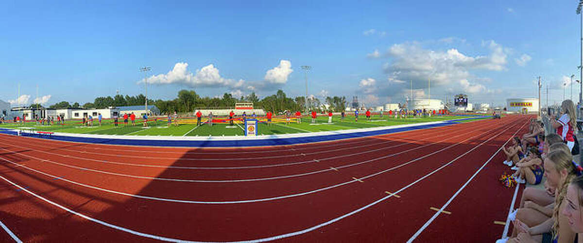 A long line of ribbon cutters on the field and part of the crowd of onlookers are shown in this panoramic photo from Friday evening's ceremonies opening the new AstroTurf playing surface at Charles Raich Field at Roxana High school.