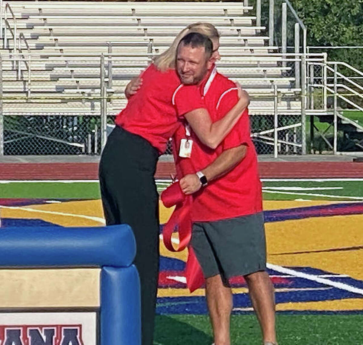Roxana Schools superintendent Deb Kreutztrager hugs Roxana High School athletic director Mark Briggs at Friday evening's ribbon cutting ceremony for the new AstroTurf playing surface at Charles Raich Field.