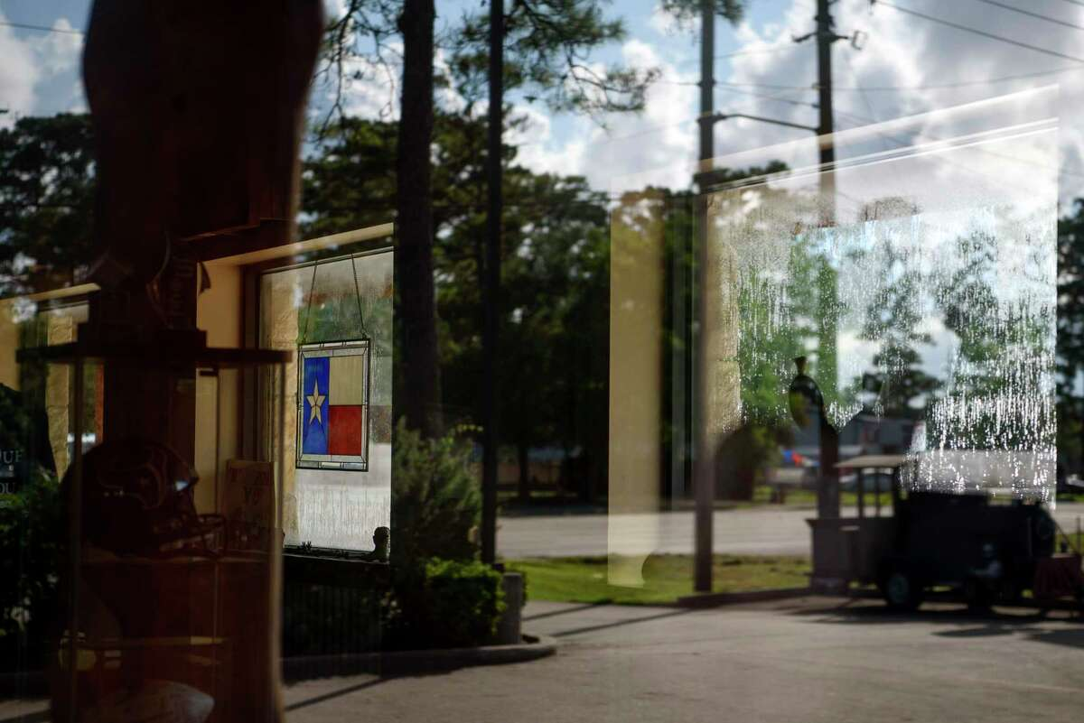 A Texas flag hangs in a window at Dickinson Barbecue & Steakhouse following the death of Scott Apley, a Dickinson city council member and official in the Texas Republican Party, due to covid-19 in Dickinson, Texas. on Aug. 14, 2021.