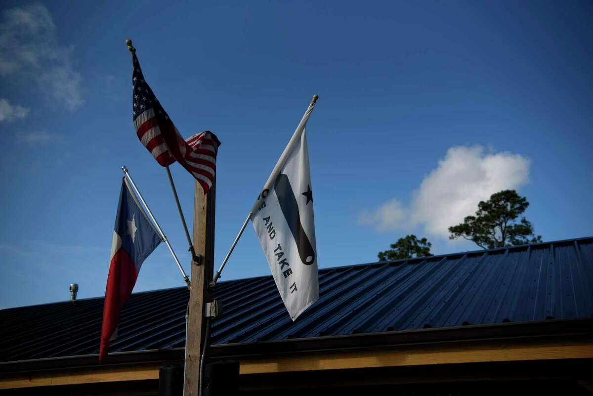 Flags fly outside Marais restaurant in Dickinson, Texas, following the death of Scott Apley, a city council member and official in the Texas Republican Party, due to covid-19.