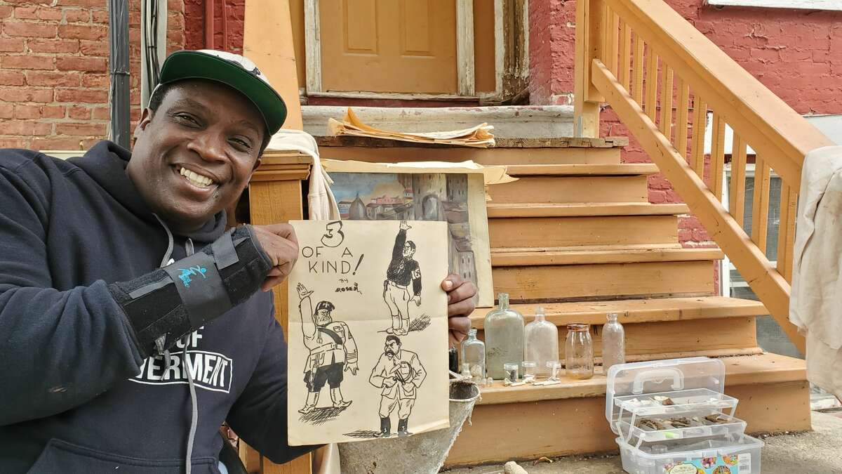 James Chaney holds a Hy Rosen sketch found in 15 Catherine St., the Albany home where both men lived as children.