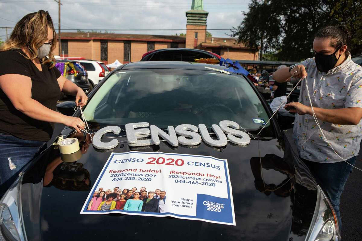 Nicole Duran, left, and her partner Melissa Allala decorate their car for the Census Bureau's vehicle parade in Third Ward on Sept. 19, 2020.