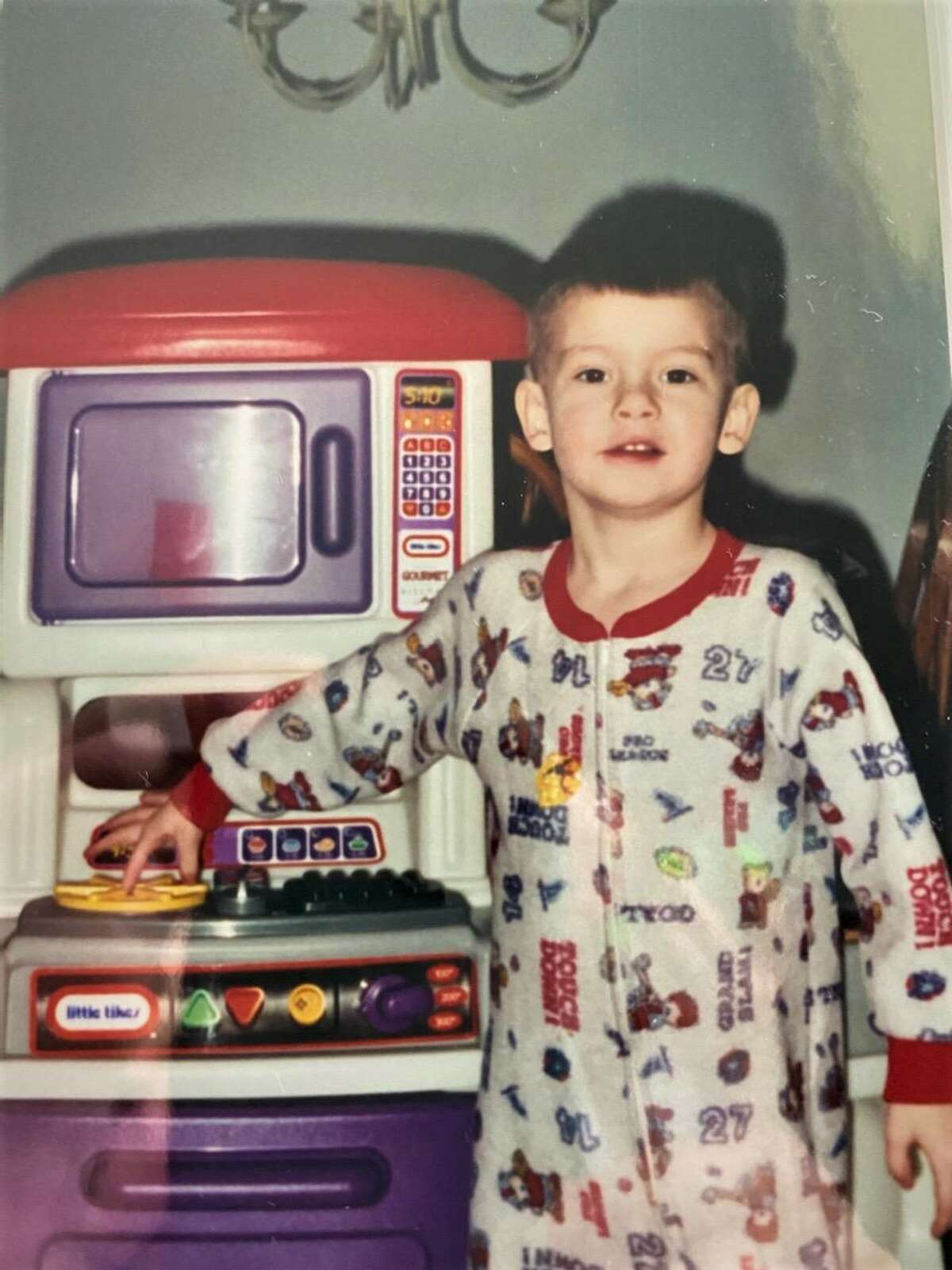 Me as a toddler next to a Fisher-Price kitchen play set.