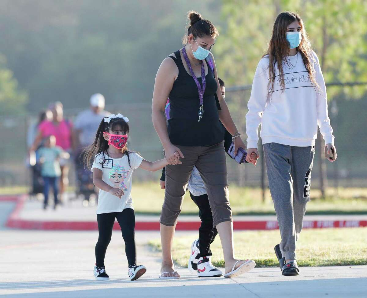 Families wear face masks as they head toward Conroe ISD's new Hope Elementary for the first day of school on Aug. 11. CISD increased its COVID-19 threat level to four the second week of school. Level five could include closing campuses if there is not enough staff to maintain school.
