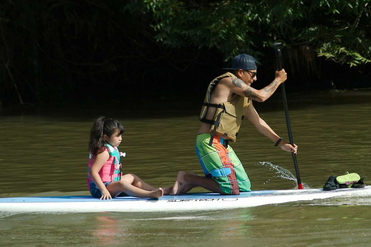 Daniel Salinas maneuvers his paddle board with his daughter Scarlette as they participate in the Clear Creek Paddle Race Saturday, Aug. 21, 2021.