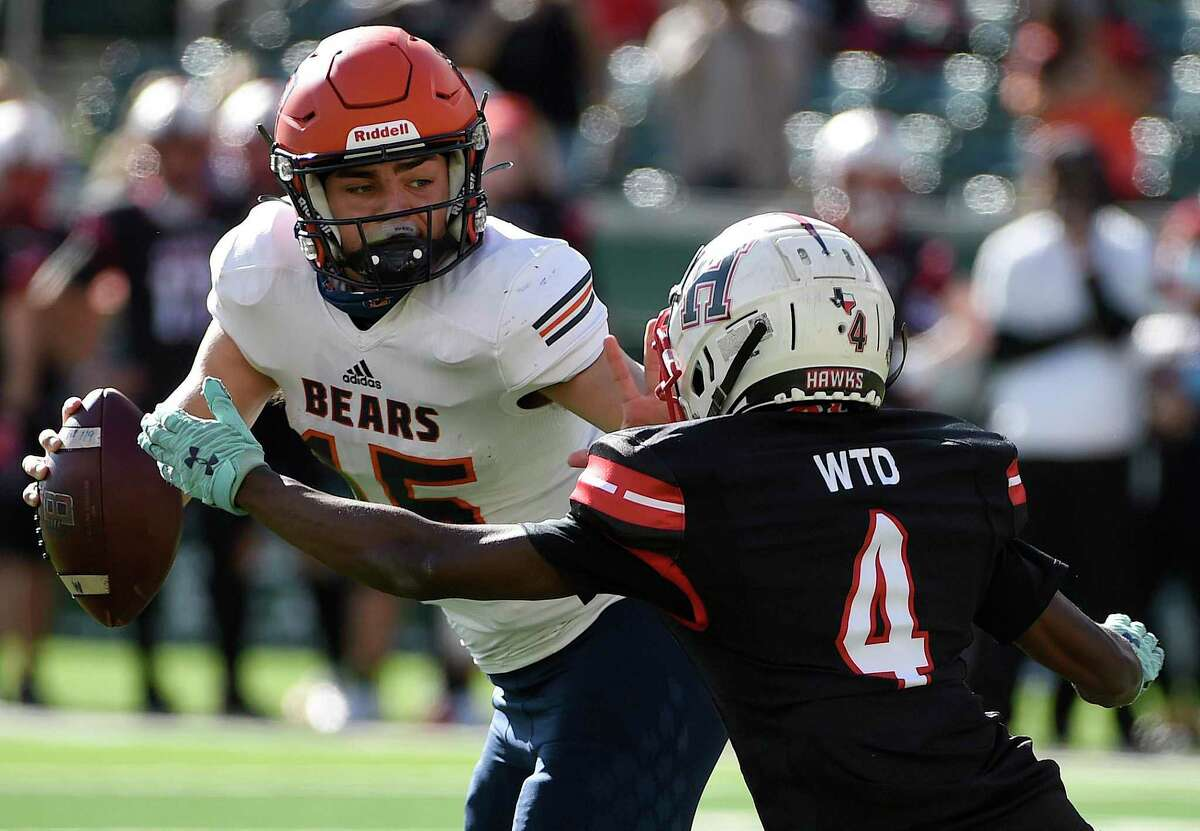 Bridgeland quarterback Conner Weigman, left, tries to escape the tackle of Rockwall-Heath defensive back Dezmon Mims during the first half of a 6A Division II Region II regional semi-final high school football playoff game, Saturday, Dec. 26, 2020, in Waco, TX.