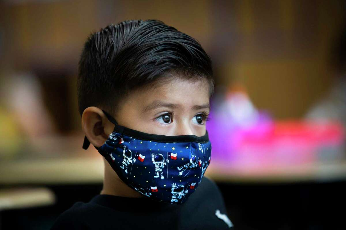 A Mahaffey Elementary School kindergarten student pays attention to his teacher while wearing a protective mask with an astronaut holding a Texas flag on Wednesday, Sept. 2, 2020, in Tomball during simulation day.