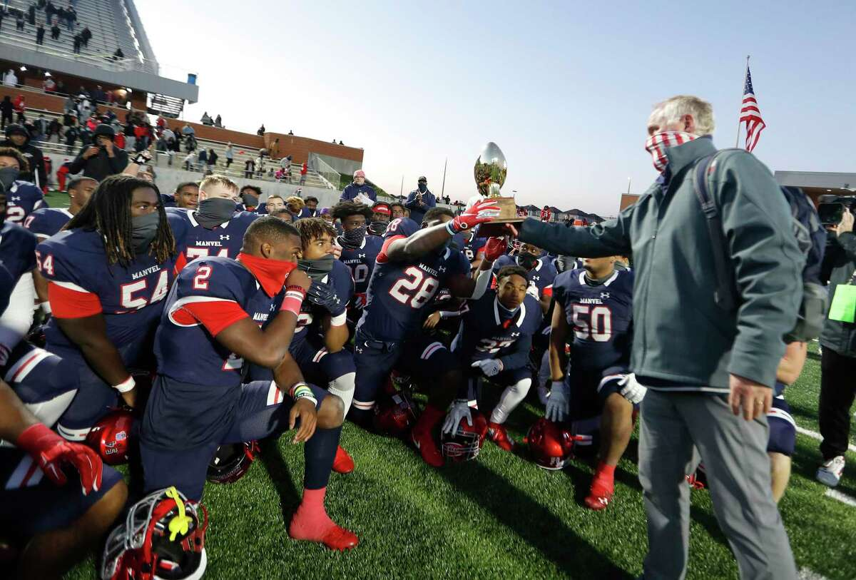 Manvel Mavericks head coach Kevin Hall hands the trophy to Jordon Vaughn (28) after Manvel's 31-7 win over Hightower Hurricanes after the 5A D1 Regional Semifinal football game at Freedom Field, Thursday, December 24, 2020, in Arcola.