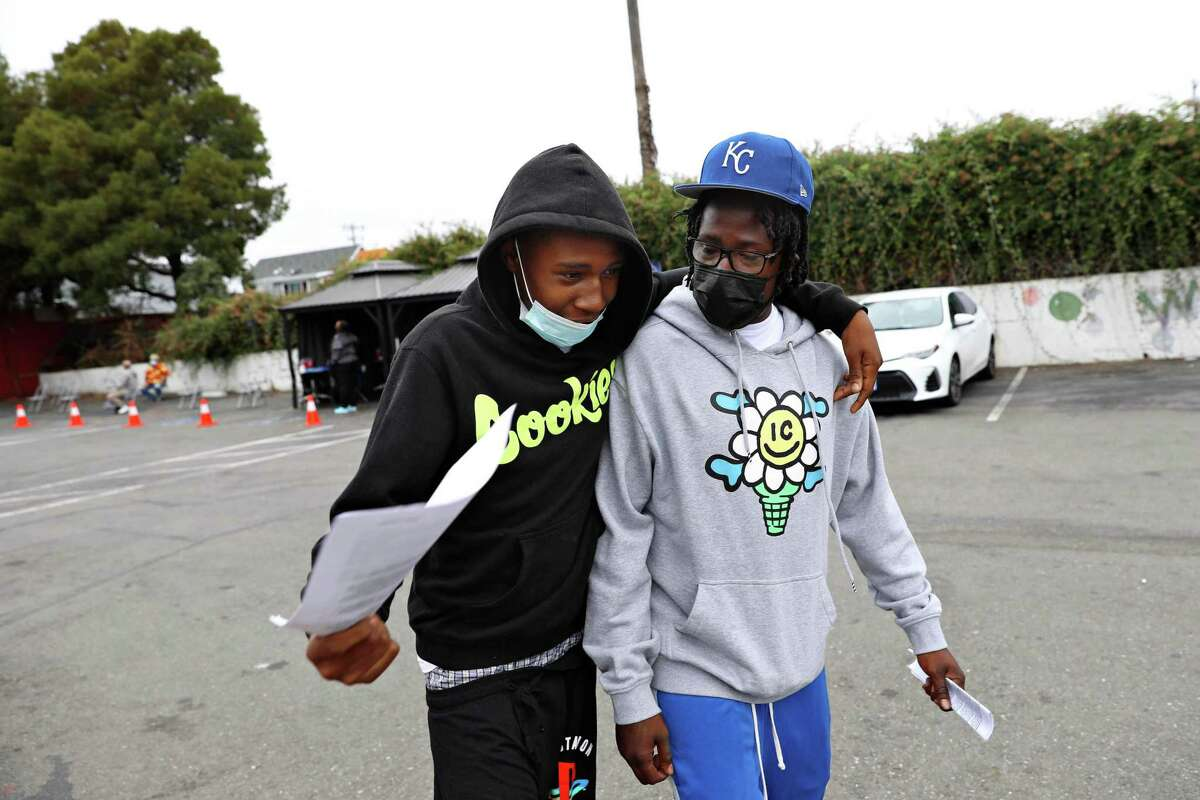 Daeshawn Johnson (l to r), 18, puts his arm around his father with his father Roshawn Johnson, both of Oakland, as they leave the vaccination clinic at LifeLong East Oakland Health Center after they both received the first dose of a COVID-19 vaccine on Wednesday, August 4, 2021 in Oakland, Calif.