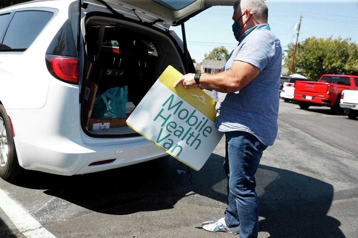 Contra Costra Health Services' Ernesto De La Torre puts a magnetic sign on side of mobile health van after arriving at Cielo Market to give COVID vaccinations in Antioch, Calif.