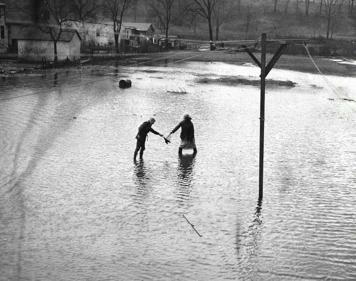 In September 1938, the Great New England Hurricane smashed coastal areas New England, including Connecticut, with a ferocity rarely seen. Pictured, a toy sailboat is passed from one person to another while waters of the Byram River in Greenwich surround them.
