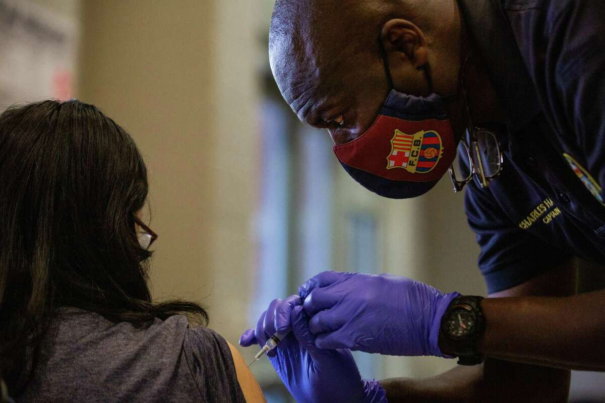 Houston Fire Department captain Charles Harper inoculates a young woman with a COVID-19 Pfizer vaccine at Hollibrook Elementary School, Saturday, Aug. 21, 2021, in Houston.