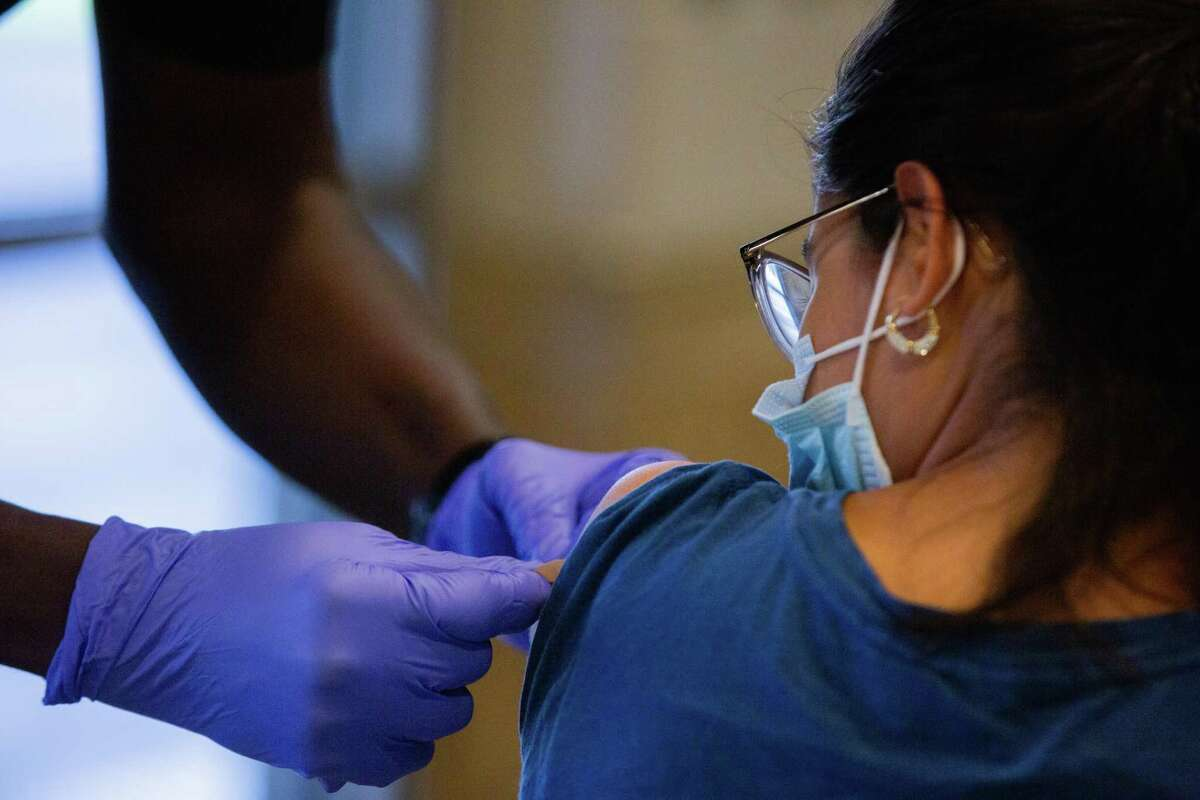 Houston Fire Department captain Charles Harper places an adhesive bandage on her arm after inoculating her with a COVID-19 Pfizer vaccine at Hollibrook Elementary School, Saturday, Aug. 21, 2021, in Houston.
