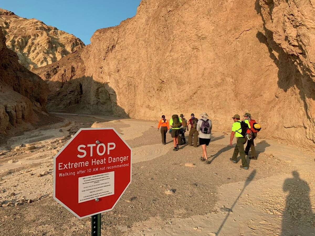 In this Wednesday, Aug. 18, 2021, photo provided by the National Park Service, an inter-agency search and rescue crew responds on foot near Red Cathedral along the Golden Canyon Trail in Death Valley National Park, Calif. Authorities say 60-year-old Lawrence Stanback died Wednesday, Aug. 18, 2021, while hiking near Red Cathedral along the Golden Canyon Trail. That day temperatures reached 108 degrees Fahrenheit.