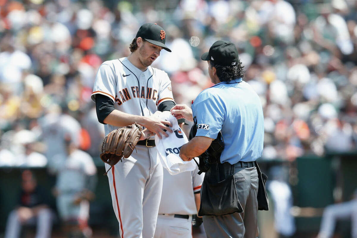 Starting pitcher Kevin Gausmanof the San Francisco Giants talks to home plate umpire Phil Cuzzi on the pitcher's mound before pitching in the bottom of the second inning against the Oakland A's on Aug. 21, 2021 in Oakland, Calif.