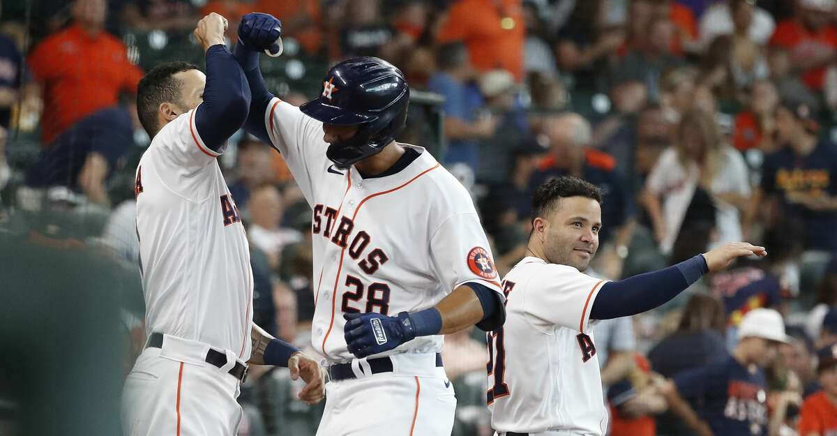 Houston Astros Taylor Jones (28) celebrates his home run off of Seattle Mariners starting pitcher Logan Gilbert with Carlos Correa (1) and Jose Altuve (27) during the fourth inning of an MLB baseball game at Minute Maid Park, Saturday, August 21, 2021, in Houston.