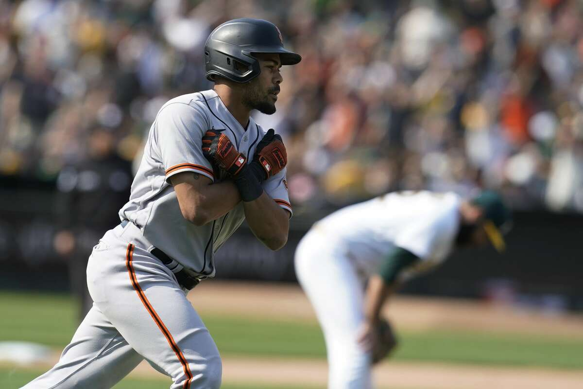 San Francisco Giants' LaMonte Wade Jr., foreground, reacts after hitting a two-run home run off Oakland Athletics' Lou Trivino, rear, during the ninth inning of a baseball game in Oakland, Calif.