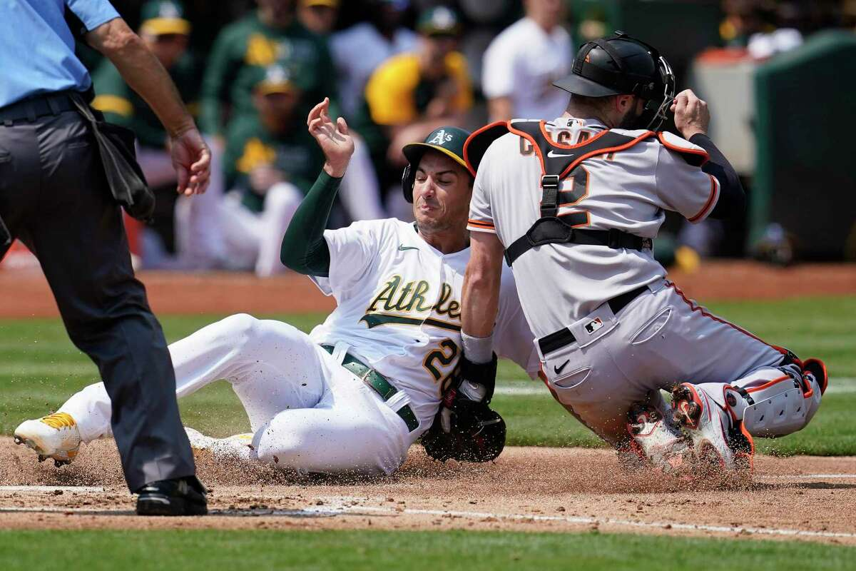 Oakland Athletics' Matt Olson, left, slides home to score against San Francisco Giants catcher Curt Casali during the third inning of a baseball game in Oakland, Calif., Saturday, Aug. 21, 2021. (AP Photo/Jeff Chiu)