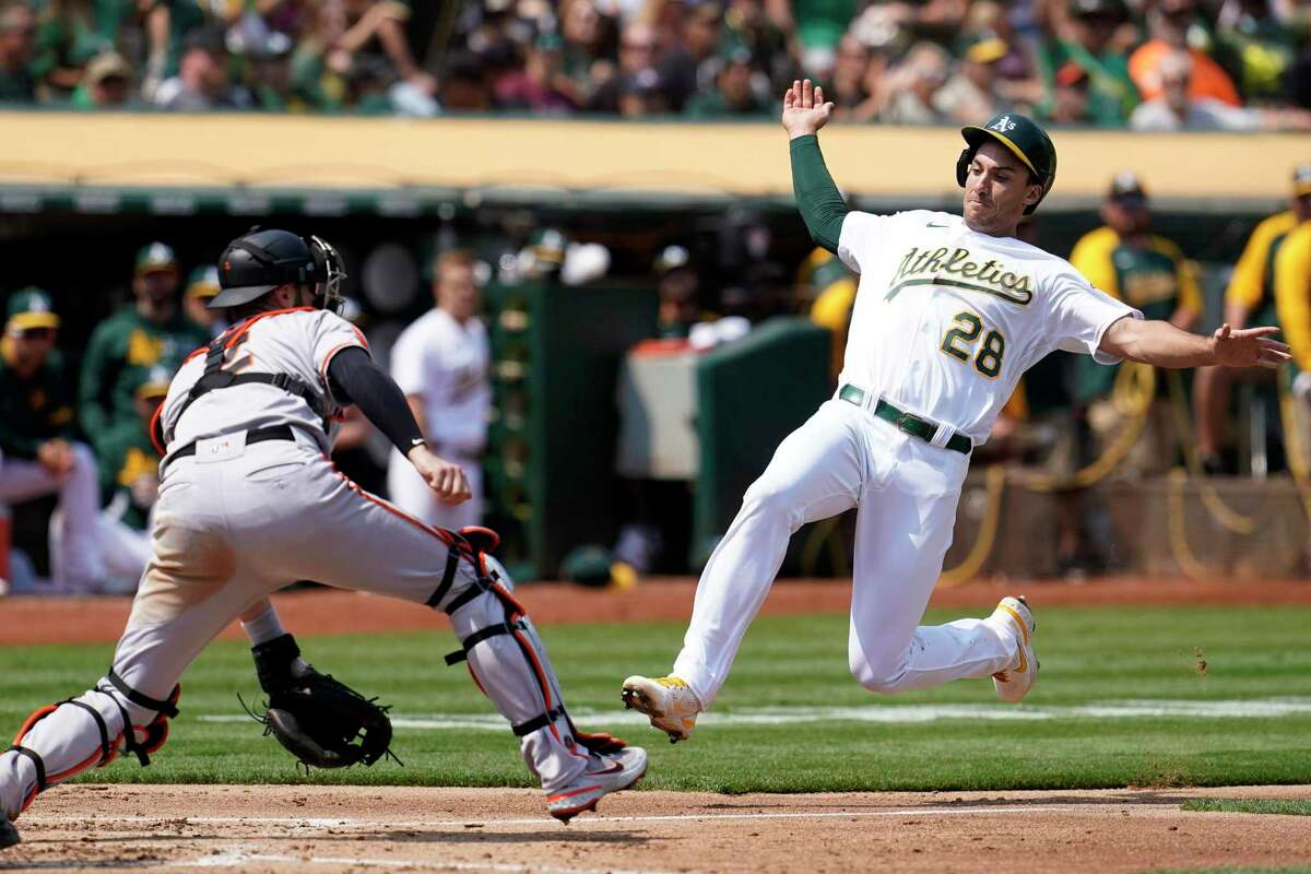 Oakland Athletics' Matt Olson (28) slides home to score against San Francisco Giants catcher Curt Casali during the third inning of a baseball game in Oakland, Calif., Saturday, Aug. 21, 2021. (AP Photo/Jeff Chiu)