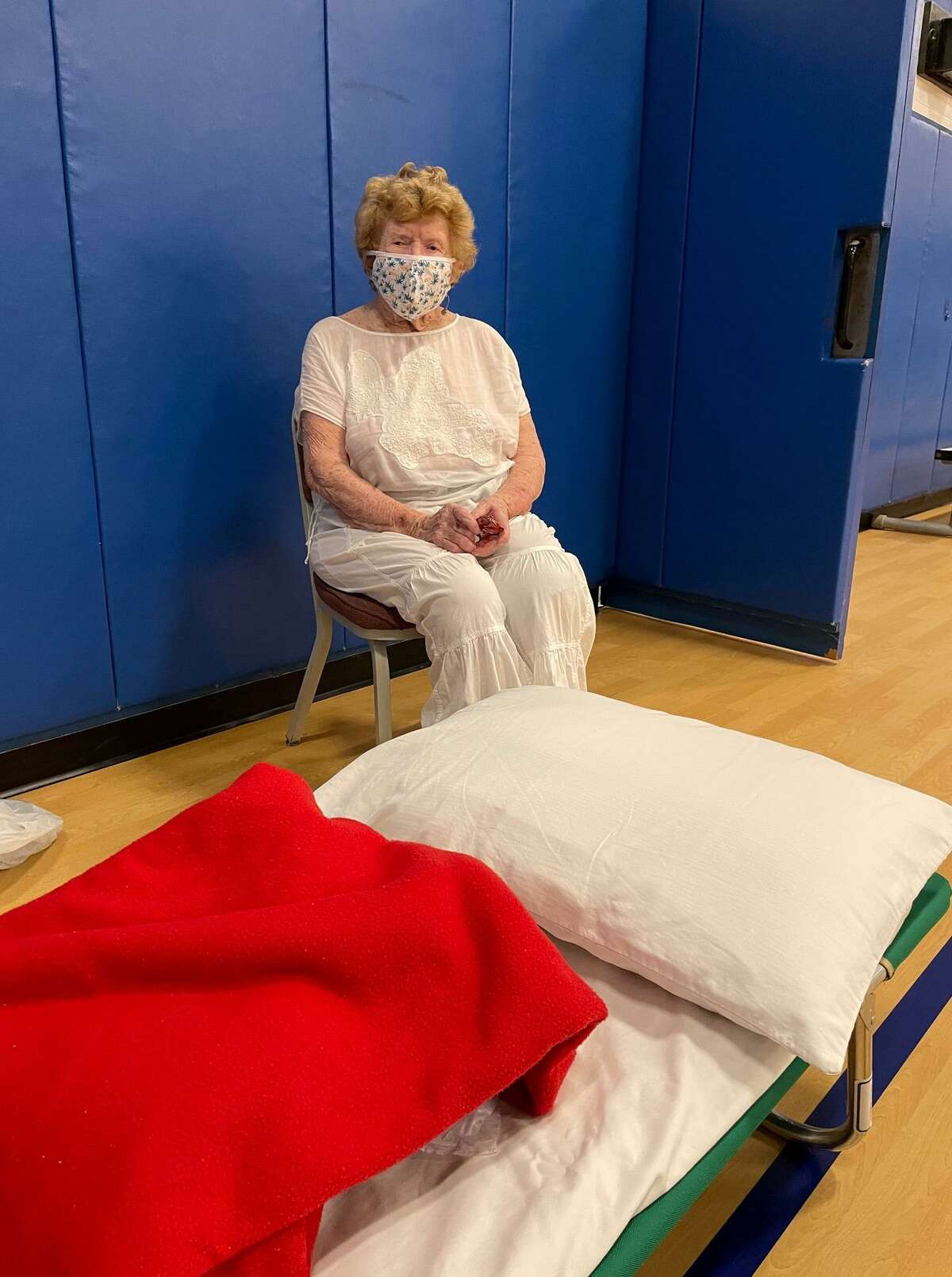 Madison resident Valerie Ryan, 99, settles into the Madison Town Campus Gym, which opened as an emergency shelter Saturday night ahead of Hurricane Henri.