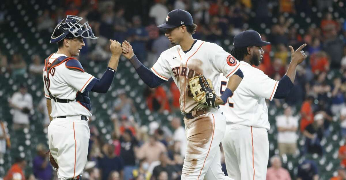 Houston Astros left fielder Taylor Jones (28) celebrates the Astros win with catcher Jason Castro (18) during the ninth inning of an MLB baseball game at Minute Maid Park, Saturday, August 21, 2021, in Houston. The Astros beat the Seattle Mariners 15-1.