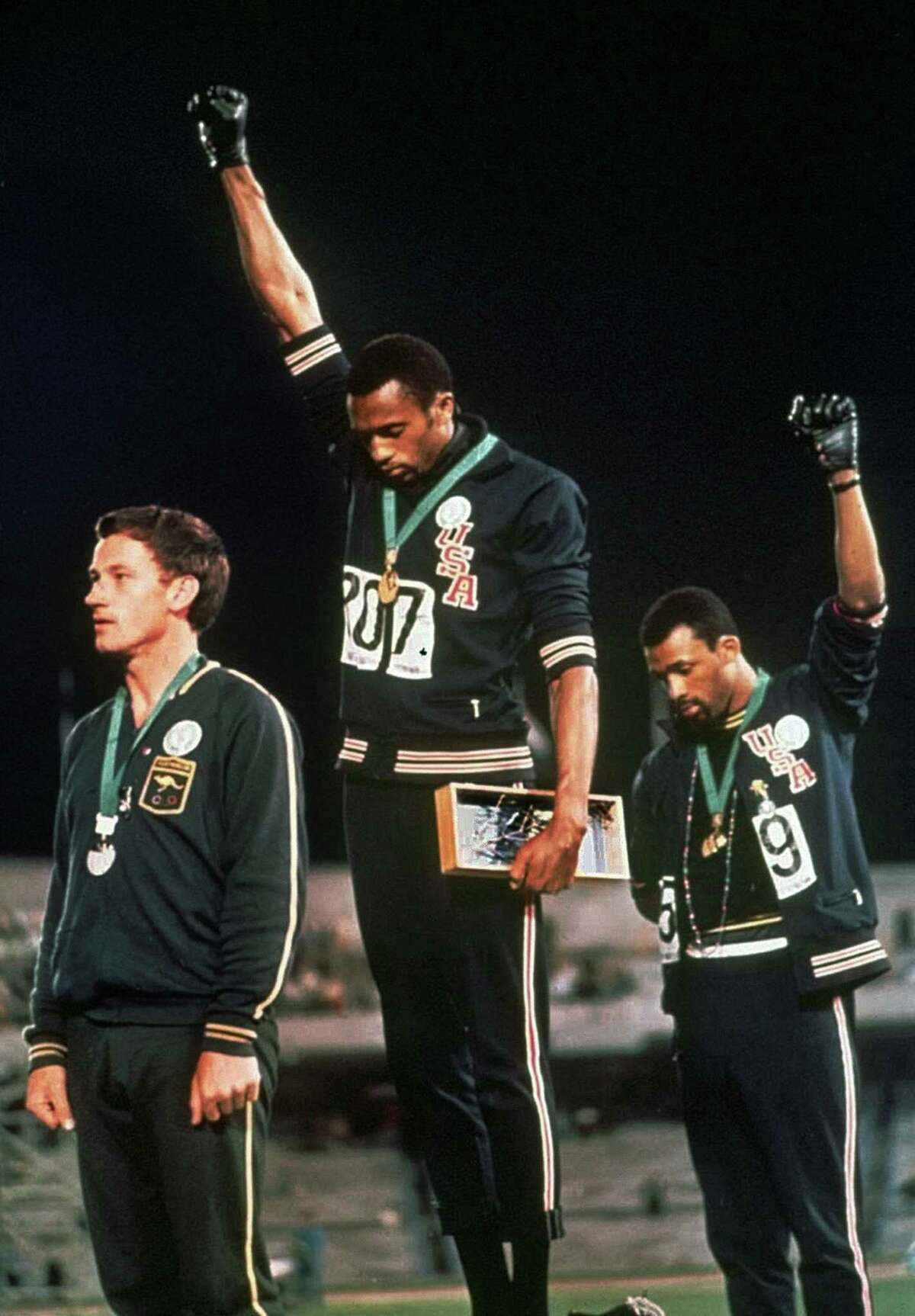 ** FILE ** Extending gloved hands skyward in racial protest, U.S. athletes Tommie Smith, center, and John Carlos stare downward during the playing of the Star Spangled Banner after Smith received the gold and Carlos the bronze for the 200 meter run at the Summer Olympic Games in Mexico City on Oct. 16, 1968. Australian silver medalist Peter Norman is at left. Peter Norman, the Australian who stood alongside the U.S. athletes staging the civil rights protest from the medal podium at the 1968 Olympics, died Tuesday October 3, 2006, of a heart attack. He was 64. (AP Photo/FILE)